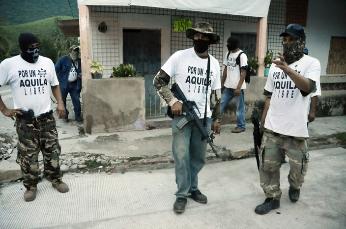 """**FILE** This photo shows armed members of a local self-defense group wearing white T-shirts with the slogan """"For a Free Aquila"""" stand at a street corner in the town of Aquila, Mexico, on  July 23, 2013. At least 23 bodies were found in two neighboring states in western Mexico where drug cartels, vigilantes and security forces have been fighting for much of the year, authorities said on Aug. 17, 2013. The state prosecutor"""