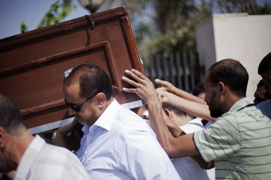 Friends and relatives of Ammar Badie, 38, killed Friday by Egyptian security forces during clashes in Ramses Square, and also son of Muslim Brotherhood's spiritual leader Mohammed Badie, carry his coffin during his funeral in al-Hamed mosque in Cairo's Katameya district on Aug. 18, 2013. Egypt increased security at the Supreme Constitutional Court building ahead of planned mass rallies by supporters of the country's ousted President Mohammed Morsi. (Associated Press)
