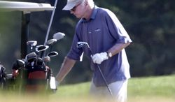 Actor Larry David returns a club to the cart while playing golf with President Obama at Farm Neck Golf Club in Oak Bluffs, Mass., on the island of Martha's Vineyard on Aug. 17, 2013. (Associated Press)