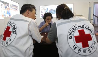 South Korean Chung Hack-soon (center), 76, talks with Red Cross officials at the headquarters of the Korea Red Cross in Seoul on Aug. 16, 2013, to fill out an application form to reunite with her family members who live in North Korea. South Korean President Park Geun-hye proposed the previous day that the two Koreas hold a reunion next month of families still separated 60 years after the Korean War, another sign of easing tensions after a spring that saw the neighbors threatening war. (Associated Press)