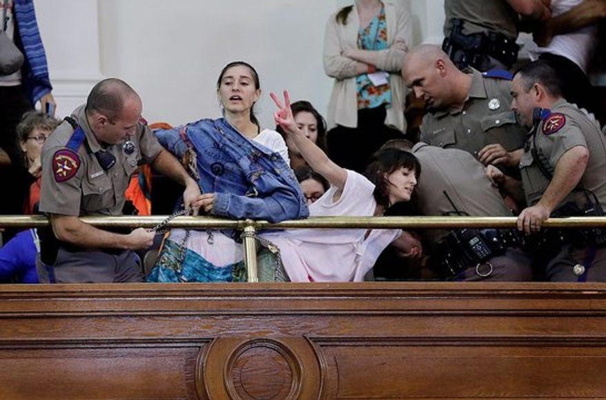 Texas state troopers remove pro-abortion demonstrators from the Texas Senate gallery during debate on a pro-life bill July 12.