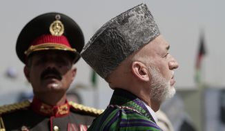 Afghan President Hamid Karzai (foreground) inspects the guard of honor during Independence Day celebrations at the Defense Ministry in Kabul, Afghanistan, on Monday, Aug 19, 2013. Mr. Karzai and Cabinet members attended a parade on Monday to mark the event, which commemorates the day Afghanistan signed a treaty with Britain in 1919 making it independent. (AP Photo/Rahmat Gul)
