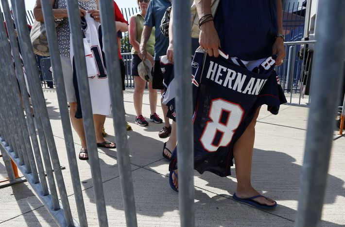 Fans line up behind a barrier to exchange their New England Patriots Aaron Hernandez football jerseys at Gillette Stadium in Foxborough, Mass., Saturday, July 6, 2013. The Patriots are offering a new jersey to al