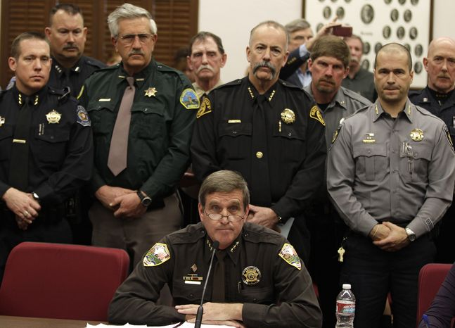 **FILE** Weld County Sheriff John Cooke (center), backed by a group of fellow sheriffs, testifies against proposed gun control legislation in the Colorado Legislature, at the State Capitol in Denver on March 4, 2013. State Senate committees began work on a package of gun-control measures that already have cleared the House which include limits on ammunition magazine sizes and expanded background che