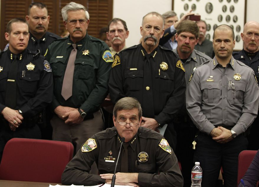 **FILE** Weld County Sheriff John Cooke (center), backed by a group of fellow sheriffs, testifies against proposed gun control legislation in the Colorado Legislature, at the State Capitol in Denver on March 4, 2013. State Senate committees began work on a package of gun-control measures that already have cleared the House which include limits on ammunition magazine sizes and expanded background checks to include private sales and online purchases. (Associated Press)