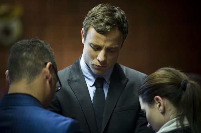 South African runner Oscar Pistorius (center) cries as he prays with his sister Aimee and brother Carl in the magistrates court in Pretoria, South Africa, on Monday, Aug. 19, 2013. Mr. Pistorius was indicted Monday on charges of murder and ille