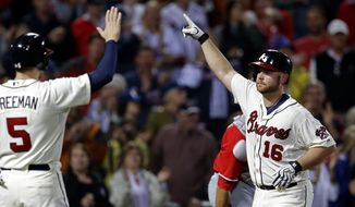 Atlanta Braves' Brian McCann, right, gestures as he is greeted at home plate by teammate Freddie Freeman, left, after they scored off McCann's two-run home run in the sixth inning of a baseball game against the Washington Nationals, Saturday, Aug. 17, 2013, in Atlanta. (AP Photo/David Goldman)