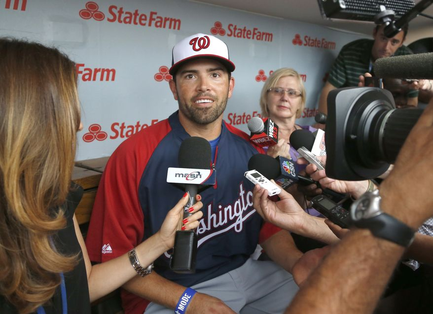 Washington Nationals' David DeJesus, center, talks with reporters after he was traded by the Chicago Cubs to the National before a baseball game between the Cubs and Nationals at Wrigley Field, Monday, Aug. 19, 2013, in Chicago. (AP Photo/Charles Rex Arbogast)