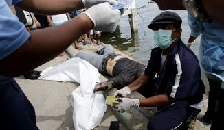 Police investigators on Monday, Aug. 19, 2013, examine the contents of the wallet of a victim of a collision between the passenger ferry MV Thomas Aquinas and the cargo ship Sulpicio Express Siete near Cebu, Philippines, on Friday night. (AP Photo/Bullit Marquez)