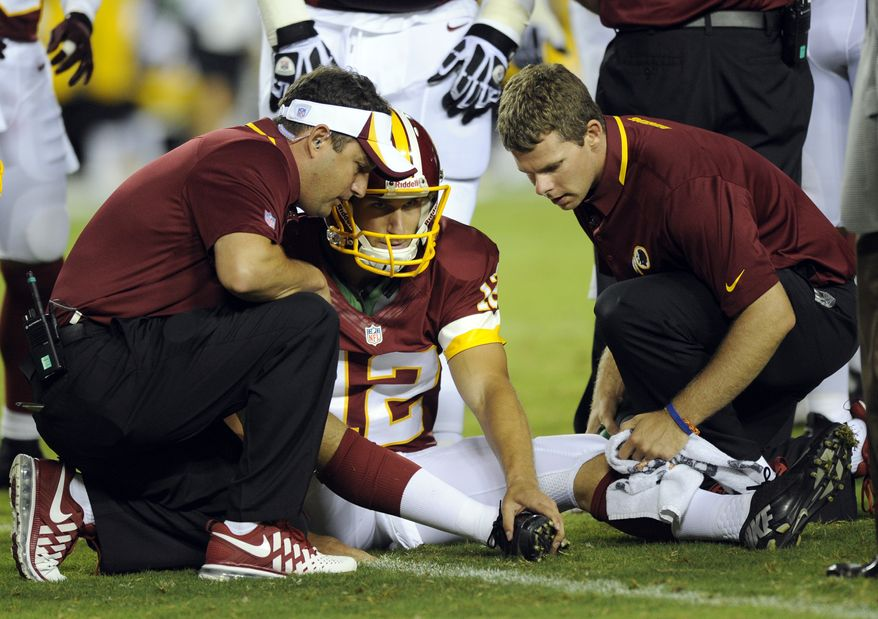 Washington Redskins quarterback Kirk Cousins (12) holds his foot as Washington Redskins medical staff examine his foot during the first half of an NFL preseason football game against the Pittsburgh Steelers Monday, Aug. 19, 2013, in Landover, Md. (AP Photo/Nick Wass)