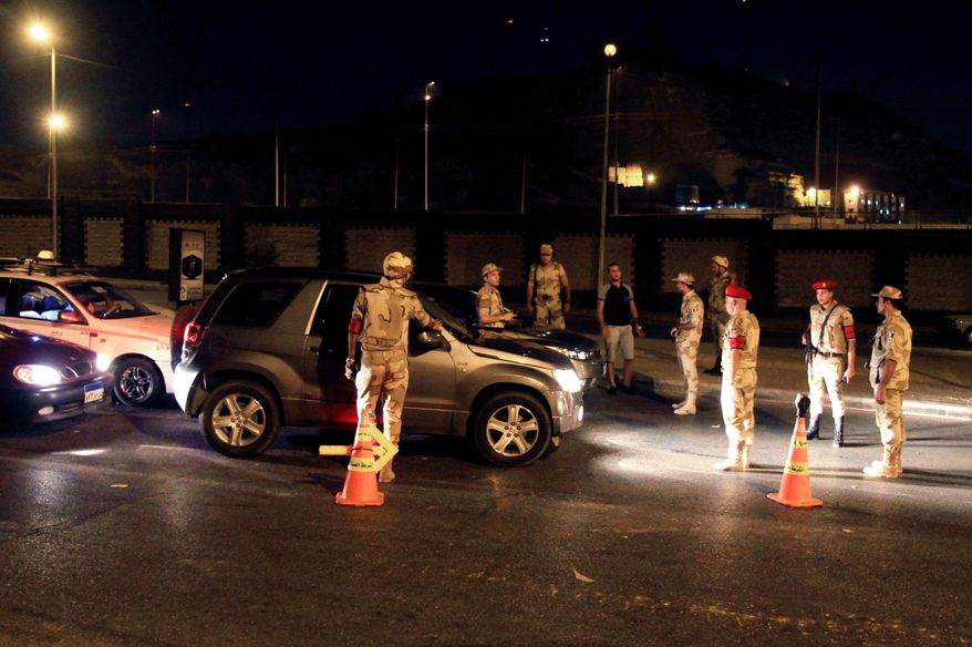 ** FILE ** Egyptian army forces search vehicles at a checkpoint during curfew in the Nasr City section of Cairo on Monday, Aug. 19, 2013. The capital remained under a state of emergency and a dusk-to-dawn curfew. (AP Photo/Ahmed Gomaa)