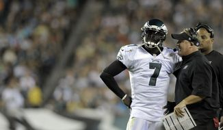Philadelphia Eagles head coach Chip Kelly talks to Michael Vick during a preseason NFL football game against the Carolina Panthers on Thursday, Aug. 15, 2013, in Philadelphia. (AP Photo/Michael Perez)