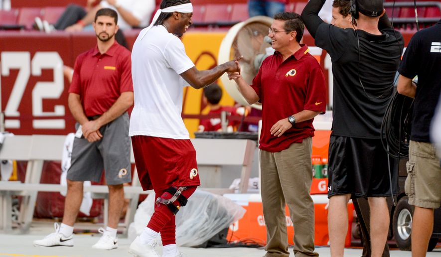 Washington Redskins quarterback Robert Griffin III (10), center left, greets Washington Redskins owner Dan Snyder, center right, during warm ups before the Washington Redskins play the Pittsburgh Steelers in NFL preseason football at FedEx Field, Landover, Md., Monday, August 19, 2013. (Andrew Harnik/The Washington Times)