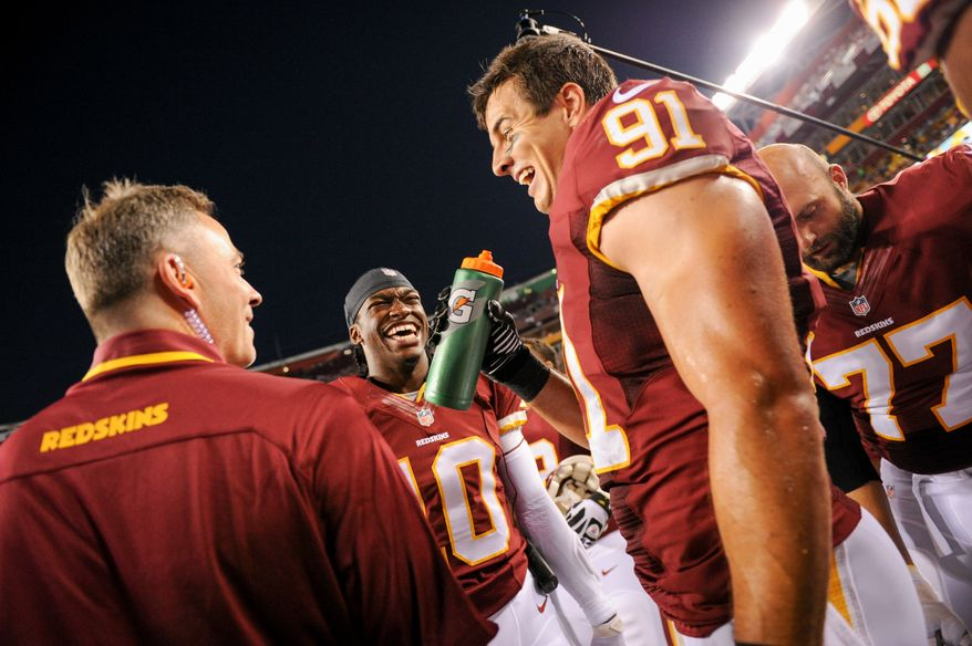 Washington Redskins quarterback Robert Griffin III (10) congratulates Washington Redskins linebacker Ryan Kerrigan (91) after he tips and intercepts a pass for a touchdown in the first quarter as the Washington Redskins play the Pittsburgh Steelers in NFL preseason football at FedEx Field, Landover, Md., Monday, August 19, 2013. (Andrew Harnik/The Washington Times)