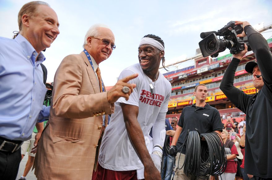 Dr. James Andrews, second from left, jokes with Washington Redskins quarterback Robert Griffin III (10) before the Washington Redskins play the Pittsburgh Steelers in NFL preseason football at FedEx Field, Landover, Md., Monday, August 19, 2013. (Andrew Harnik/The Washington Times)