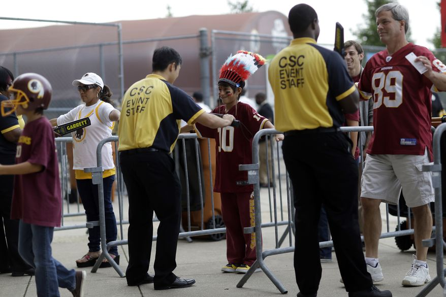 Security personnel screen fans as they enter before an NFL football game between the Washington Redskins and the Pittsburgh Steelers Monday, Aug. 19, 2013, at FedEx Field in Landover, Md. (AP Photo/Patrick Semansky)