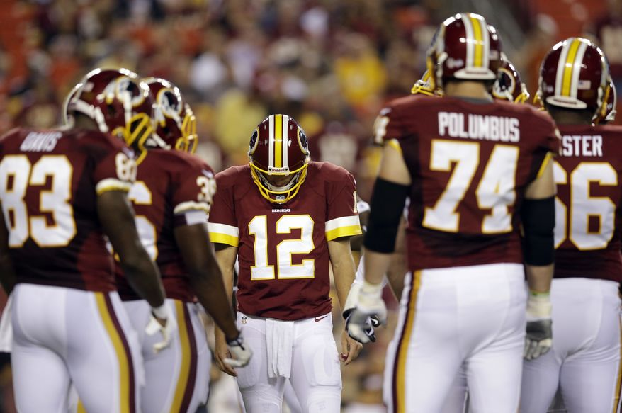 Washington Redskins quarterback Kirk Cousins walks into a huddle with teammates during the first half of an NFL preseason football game against the Pittsburgh Steelers Monday, Aug. 19, 2013, in Landover, Md. (AP Photo/Patrick Semansky)