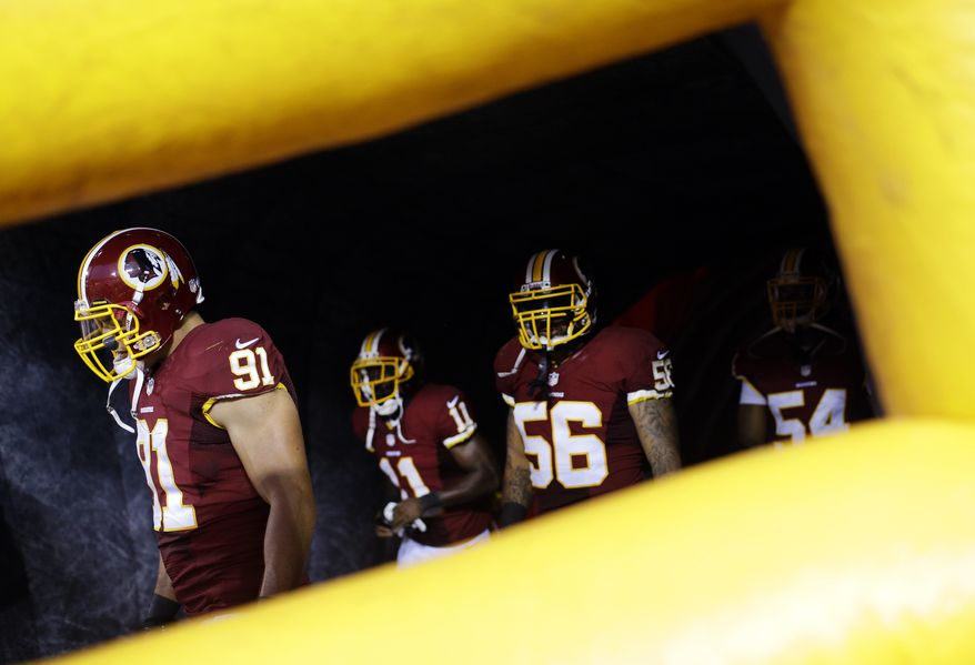 Washington Redskins linebacker Ryan Kerrigan (91) walks out of a tunnel with teammates before an NFL preseason football game against the Pittsburgh Steelers Monday, Aug. 19, 2013, in Landover, Md. (AP Photo/Patrick Semansky)