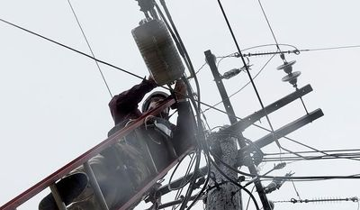 Cable TV worker Fred Harris does maintenance on lines in this 2012 photo. (Barbara L. Salisbury/The Washington Times)