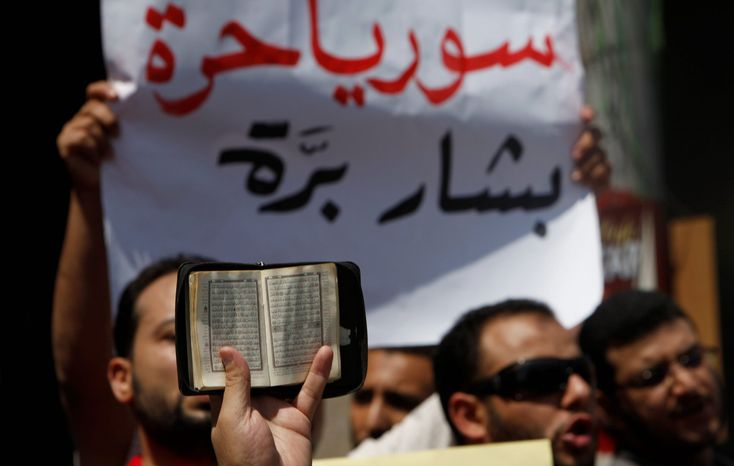 "A member of Egypt's Muslim Brotherhood raises the Koran in front of a banner that reads ""Bashar go out Syria is free."" The Brotherhood has emerged as one of the better-organized opponents of the Syrian regime. (Associated Press)"