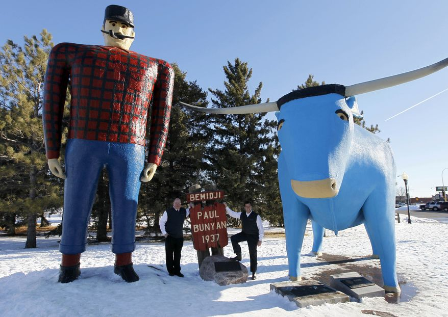 """**FILE** Republican presidential candidate and former Pennsylvania Sen. Rick Santorum (right) stands below the Paul Bunyan and Babe the Blue Ox statues with Bill Batchhelder during a campaign stop in Bemidji, Minn., on Feb. 5, 2012. Bachhelder's company, Bemidji Woolen Mills, manufactures the official """"Santorum for President"""" sweater vest. (Associated Press)"""