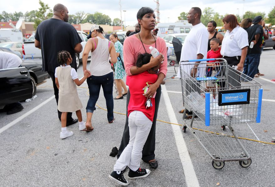 Keondria Williams holds on tight to her daughter, Kierstin, 8, after they were reunited in a Wal-Mart parking lot on Tuesday afternoon, Aug. 20, 2013, after McNair Discovery Learning Academy in Decatur, Ga., was evacuated because of a gunman who fired shots from inside the school. (AP Photo/Atlanta Journal-Constitution, Ben Gray)