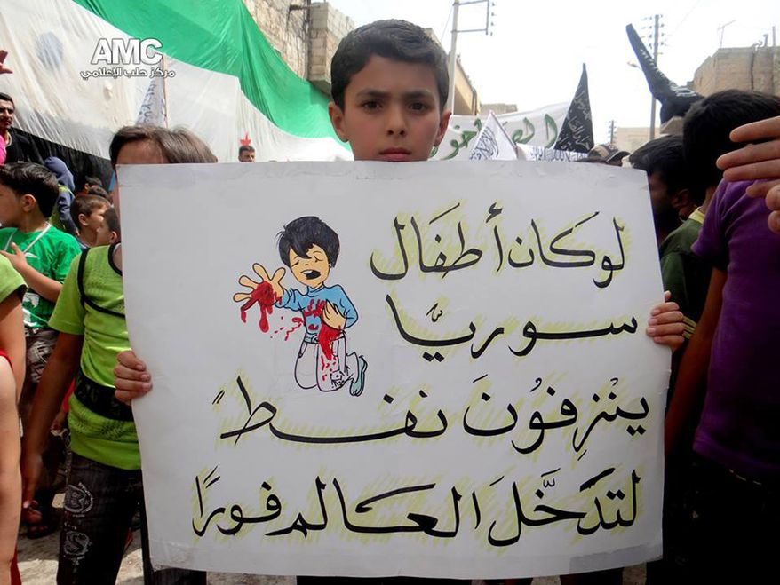 """A citizen journalism image provided by Aleppo Media Center, authenticated based on its contents and other AP reporting, shows a Syrian boy holding an Arabic placard that reads: """"if Syria's children bled petrol, the entire world would have intervened,"""" during a demonstration against the alleged chemical weapons attack at the suburbs of Damascus, in Aleppo on Aug. 21, 2013. Syrian anti-government activists accused the regime of carrying out a toxic gas attack that killed at least 100 people, including many children as they slept, during intense artillery and rocket barrages on the eastern suburbs of Damascus, part of a fierce government offensive in the area. (Associated Press/Aleppo Media Center)"""