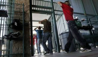 **FILE** Illegal immigrants file into a U.S. Border Patrol facility in Tucson, Ariz. (Associated Press)