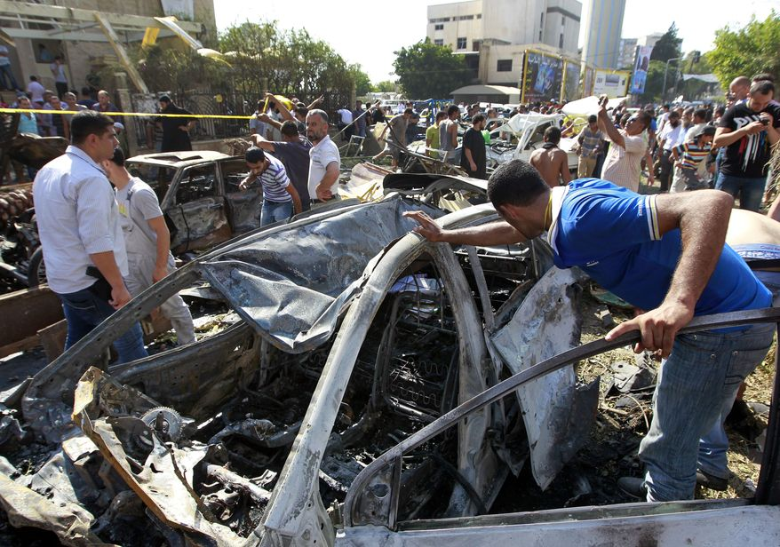 People gather outside of the Salam mosque amid charred cars and wide damage, in the northern city of Tripoli, Lebanon, on Aug. 23, 2013. The twin car bombs, which killed dozens hit amid soaring tensions in Lebanon as a result of Syria's civil war, which has sharply polarized the country along sectarian lines and between supporters and opponents of the regime of Syrian President Bashar Assad. It was the second such bombing in just over a week, showing the degree to which the tiny country is being consumed by the raging war next door. (Associated Press)