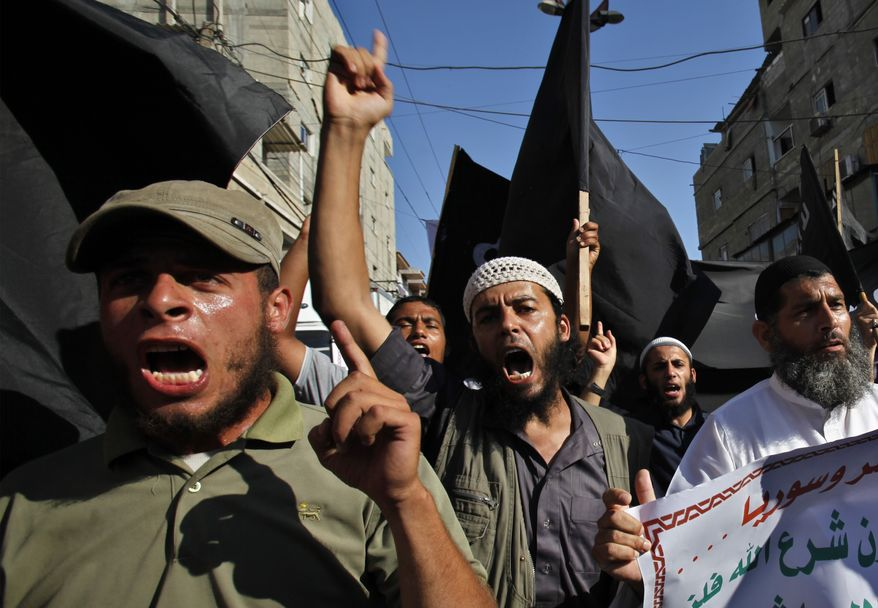 """Palestinian members from Youth Salafists group chant slogans while waving their black flags during a protest against the Egyptian and Syria regimes in Rafah Refugee Camp, southern Gaza Strip, on Aug. 22, 2013. Arabic on poster reads """"Criminals and murderers."""" Syrian government forces pressed their offensive in eastern Damascus on Thursday, bombing rebel-held suburbs where the opposition said the regime had killed more than 100 people the day before in a chemical weapons attack. The government has denied allegations it used chemical weapons in artillery barrages on the area known as eastern Ghouta, calling the charges """"absolutely baseless."""" (Associated Press)"""