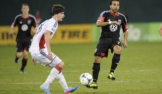 **FILE** D.C. United midfielder Dwayne De Rosario (7) kicks the ball against New England Revolution midfielder Stephen McCarthy, left, during the second half of an MLS soccer game, Saturday, July 27, 2013, in Washington. The New England Revolution won 2-1. (AP Photo/Nick Wass)