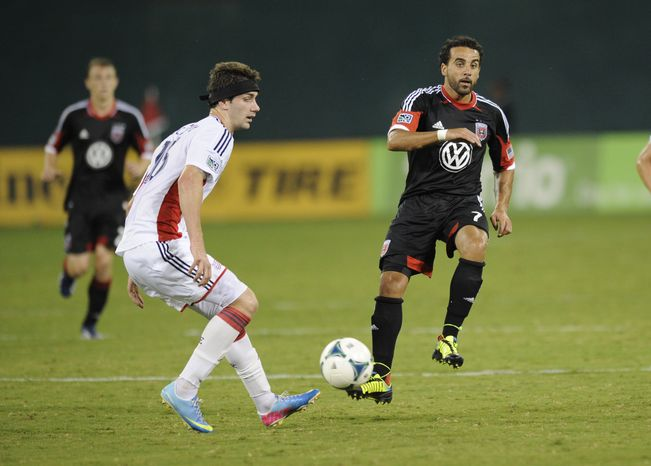 **FILE** D.C. United midfielder Dwayne De Rosario (7) kicks the ball against New England Revolution midfielder Stephen McCarthy, left, during the second half of an MLS soccer game, Saturday, July 27, 2013, in Washington. The New England Revolution won 2-1. (AP Photo/N