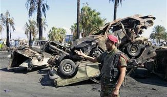 ** FILE ** A Lebanese Army soldier stands guard in front of damaged cars at the site of a car bomb explosion outside of the Al-Taqwa mosque, in the northern city of Tripoli, Lebanon, Saturday, Aug. 24, 2013. (AP Photo/Bilal Hussein)