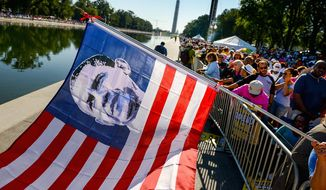An American flag picturing President Obama in place of the 50 stars is held as a crowd gathers along the Reflecting Pool on Saturday to mark the 50th anniversary of the March on Washington. Visitors also went to the Martin Luther King Jr. Memorial (below). Anniversary events continue through Wednesday when Mr. Obama will speak. Some who went to the original march are returning for the anniversary. (PHOTOGRAPHS BY andrew harnik/the washington times)