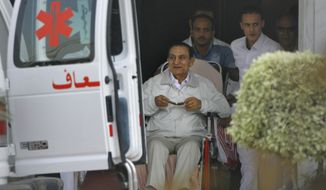 Former Egyptian President Hosni Mubarak (seated), 85, is escorted by medical and security personnel into an ambulance to be taken by helicopter ambulance from Maadi Military Hospital to the Cairo Police Academy for trial on Sunday, Aug. 25, 2013, in Cairo. Mr. Mubarak, under house arrest after being released from detention last week, is being retried on charges of complicity in the killings of protesters during the 2011 Egyptian uprising. (AP Photo/Amr Nabil)