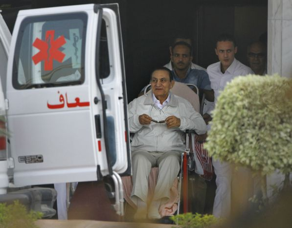 Former Egyptian President Hosni Mubarak (seated), 85, is escorted by medical and security personnel into an ambulance to be taken by helicopter ambulance from Maadi Military Hospital to the Cairo Police Academy for trial on Sunday, Aug. 25, 2013, in Cairo. Mr. Mubarak, under house arrest after being released from
