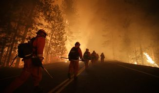 Inmate firefighters walk along state Highway 120 as firefighters continue to battle the Rim Fire near Yosemite National Park in Northern California on Sunday, Aug. 25, 2013. Fire crews are clearing brush and setting sprinklers to protect two groves of giant sequoias as a massive week-old wildfire rages along the remote northwest edge of the park. (AP Photo/Jae C. Hong)