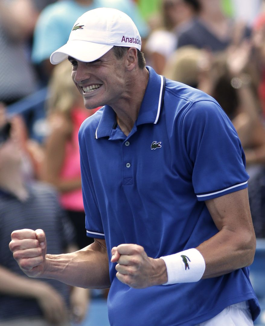 John Isner celebrates after upsetting top seeded Novak Djokovic, from Serbia, 7-6 (5), 3-6, 7-5, in a quarterfinal match at the Western & Southern Open tennis tournament, Friday, Aug. 16, 2013, in Mason, Ohio. (AP Photo/Al Behrman)