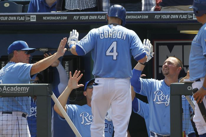 Kansas City Royals' Alex Gordon (4) is congratulated by manager Ned Yost, left, and Billy Butler, right, after hitting a home run off Washington Nationals pitcher Dan Haren in the first inning of a