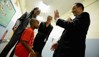 "D.C. Mayor Vincent C. Gray stops for a high-five from first-grader Jaiair Wade, 5, as he walks with Principal Rebecca Crouch (left) at DC Scholars Public Charter School. ""To go to school after school and see them engaging like it's the second week and not the first day, it's tremendously uplifting,"" Mr. Gray said."