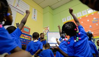 Kindergarten teacher Nick Brooks calls on eager students who raise their hands during a lesson in his classroom on the first day of school at DC Scholars Public Charter School in Southeast on Monday. A couple of accidents involving school buses marred the morning for some students, but there were no serious injuries. (Photographs by Andrew Harnik/The Washington Times)