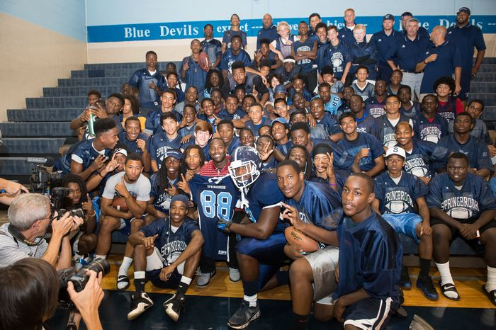 Redskins receiver Pierre Garcon poses with players on the Springbrook High School football team after providing them with new uniforms on Aug. 20, 2013 as part of his partnership with Russell Athletic