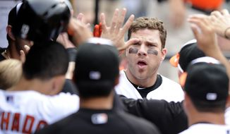 Baltimore Orioles' Chris Davis celebrates his two-run home run in the dugout during the eighth inning of a baseball game against the Colorado Rockies, Sunday, Aug. 18, 2013, in Baltimore. The Orioles won 7-2. (AP Photo/Nick Wass)