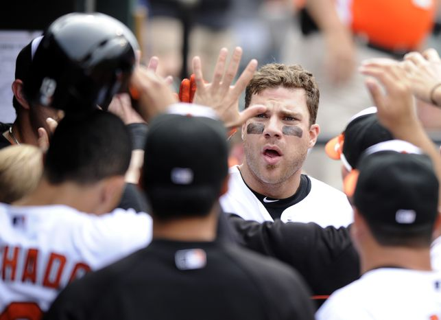 Baltimore Orioles' Chris Davis celebrates his two-run home run in the dugout during the eighth inning of a baseball game against the Colorado Rockies, Sunday, Aug. 18,