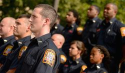 Andrew Harnik/The Washington Times D.C. firefighters and paramedics listen to Mayor Vincent C. Gray and Chief Kenneth B. Ellerbe announce the hiring paramedics and the purchase of 30 new ambulances by the end of the year.