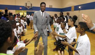 Milwaukee Bucks player Larry Sanders (center) gets high-fives from members of the Boys & Girls Club as he enters the gymnasium before his news conference at the club's Pieper-Hillside branch in Milwaukee on Monday, Aug. 26, 2013. Sanders, who discussed his new four-year contract extension, also donated and handed out several hundred backpacks filled with school supplies to club members. (AP Photo/Milwaukee Journal Sentinel, Mike De Sisti)
