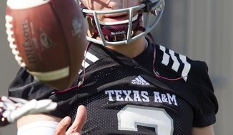 FILE - In this Aug. 5, 2013 file photo, Texas A&M quarterback and Heisman Trophy winner Johnny Manziel warms up during football practice in College Station, Texas. Allegations that Manziel received payment for autographs could threaten his eligibility along with A&M's season and have some in College Station fed up with his antics. (AP Photo/Patric Schneider, File)