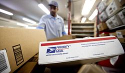 Packages await sorting at a post office in Atlanta as U.S. Postal Service letter carrier Michael McDonald gathers mail to load into his truck before making his delivery run on Thursday, Feb. 7, 2013. (AP Photo/David Goldman)