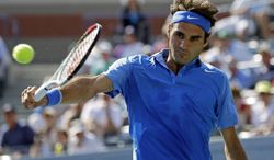 Roger Federer, of Switzerland, returns a shot to Grega Zemlja, of Slovenia, during the first round of the 2013 U.S. Open tennis tournament Tuesday, Aug. 27, 2013, in New York. (AP Photo/Mike Groll)