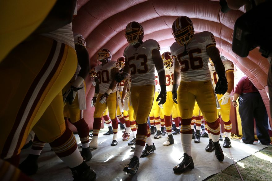 Members of the Washington Redskins walk through a tunnel to the field before an NFL preseason football game against the Buffalo Bills Saturday, Aug. 24, 2013, in Landover, Md. (AP Photo/Patrick Semansky)